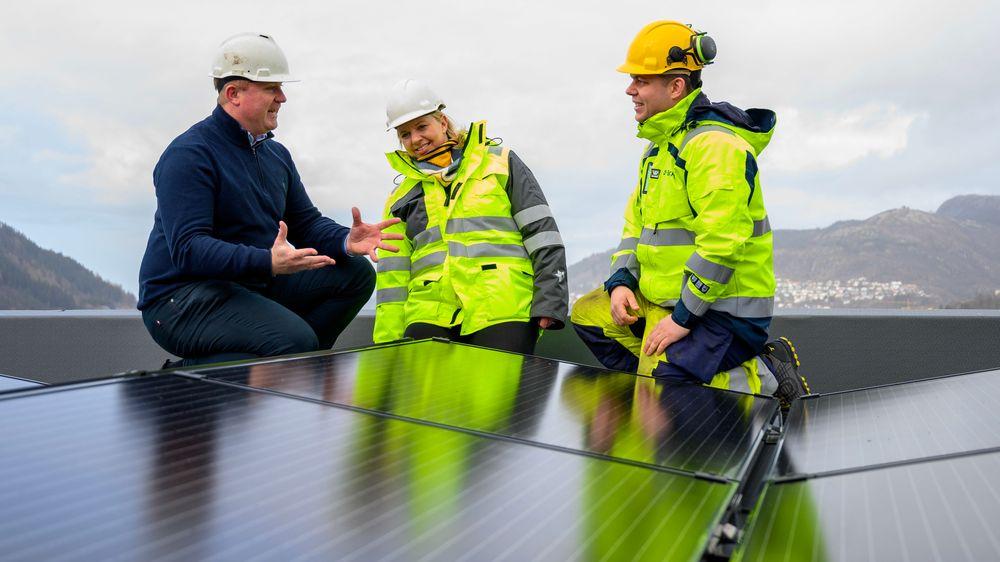 Prosjektleder Tomas Plassen (f.v.) og daglig leder Marie Therese Heldal Haukeland i Heldal Eiendom diskuterer solcellepanelene på taket av bygget på Slettebakken med Kjetil Strand Solheim, prosjektansvarlig og byggeleder i BKK.