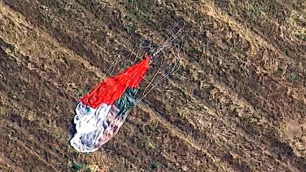 Pilotens fallskjerm ligger etterlatt på et jorde. Han overlevde etter å ha skutt seg ut av jetflyet sitt, som siden styrtet i et varehus.
