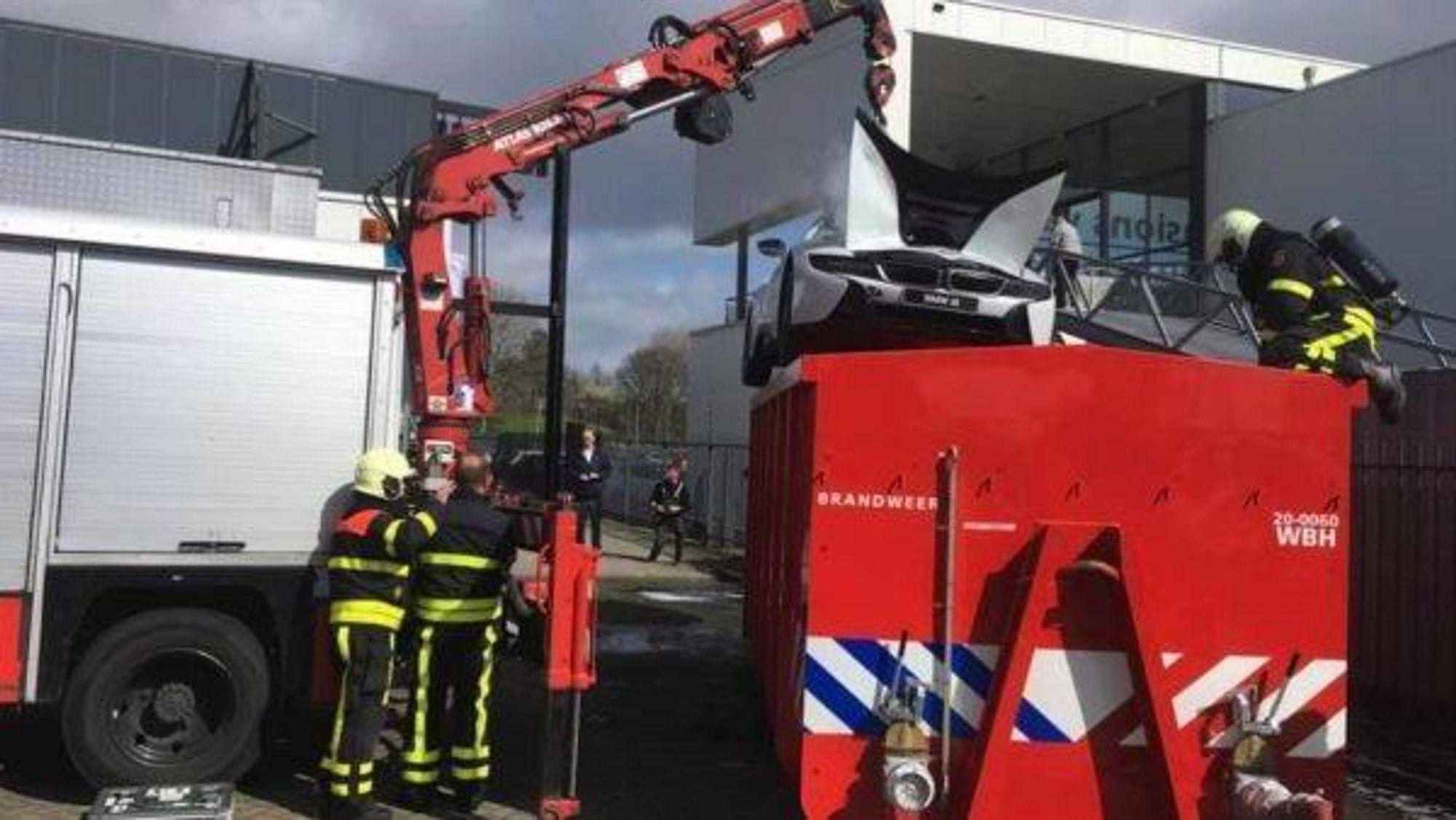 Brannfolk senker en BMW i8 plug-in hybrid ned i en container med vann for å kjøle ned en brann i bilens lithium-ion batteri.