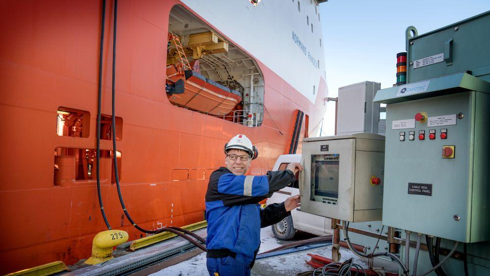 Ankerhåndtereren Normand Ranger kobler seg på landstrømanlegget på Skoltekaien i Bergen. Elektriker Jarl Svoren må inn i skapet og koble til strømmen.