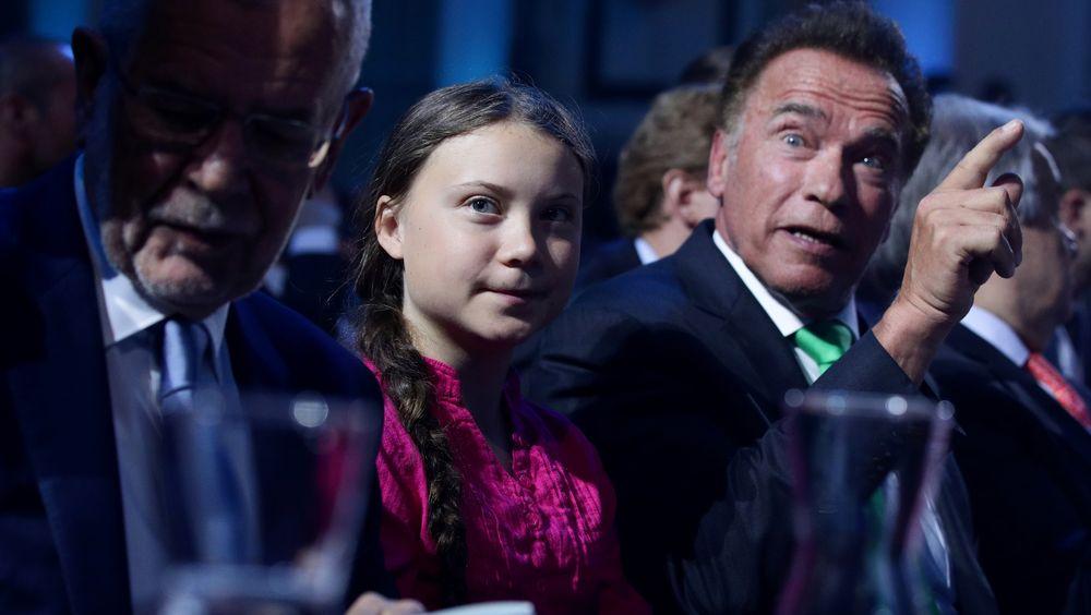 Den østerrikske presidenten Alexander van der Bellen (t.v.) er praktisk talt i skyggen av klimaaktivist Greta Thunberg og tidligere California-guvernør Arnold Schwarzenegger (rep.)  på verdenskonferanse i Wien i slutten av mai.