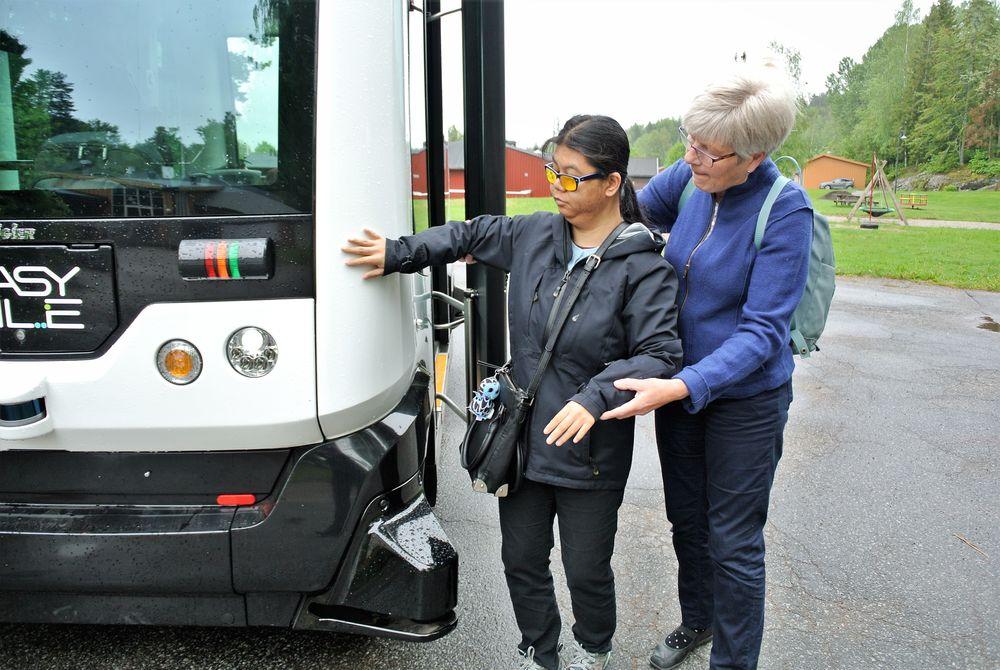 Døvblinde Rachada Chotsuk bruker hendene til å bli kjent med bussen før hun går ombord. Her får hun hjelp av Inger Svendsen.