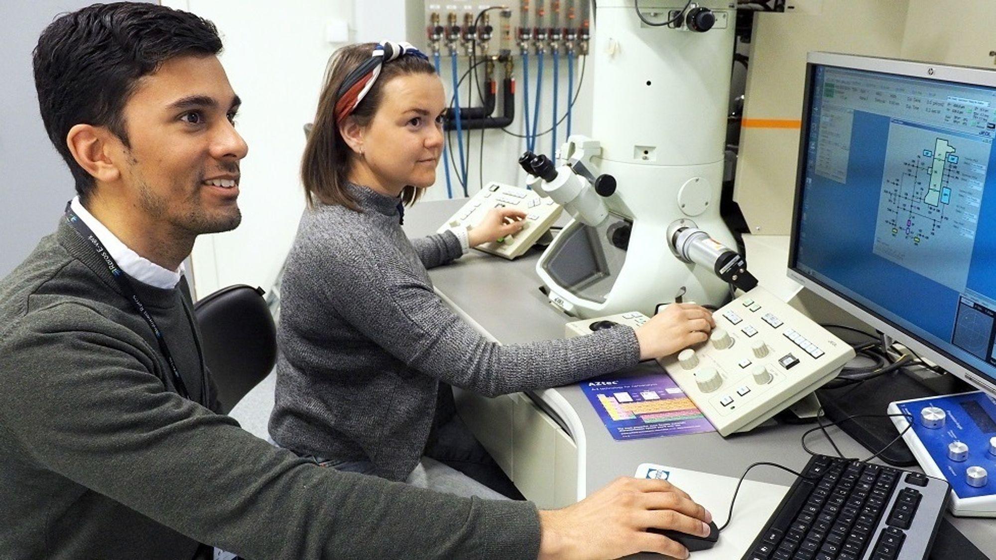 Adrian Lervik og Elisabeth Thronsen bruker elektronmikroskop for å undersøke strukturen i aluminiumslegeringer.