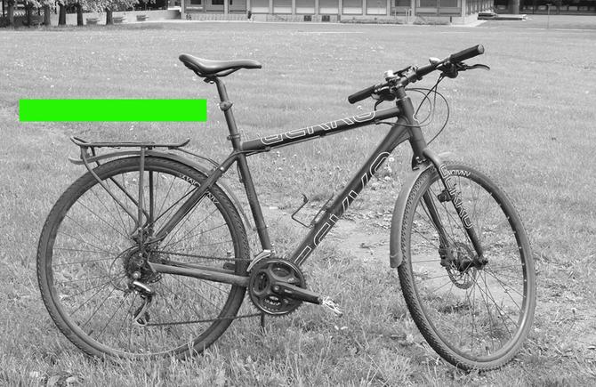 Svart/hvitt-bilde av sykkel, med bred grønn strek tegnet på bildet - rett over bagasjebrettet.