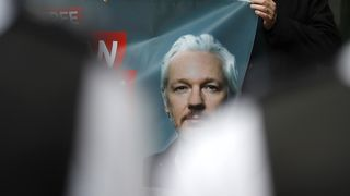Plakat med bilde av Julian Assange under en demonstrasjon utenfor domstolen i London fredag.