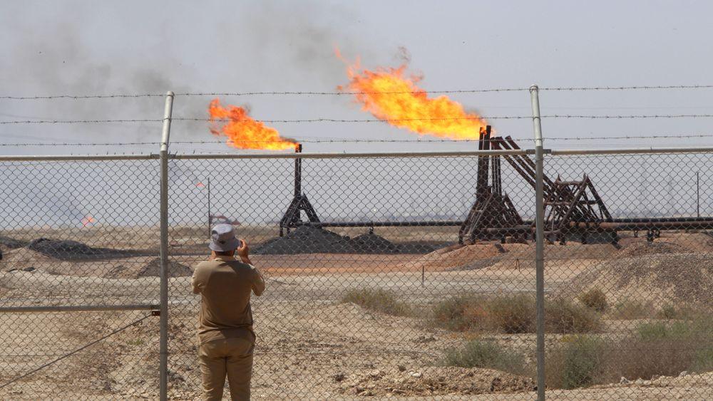 Illustrasjonsbilde: En journalist tar bilde av Exxons oljefelt West Qurna-1 nærme Basra 17. juni 2019.
