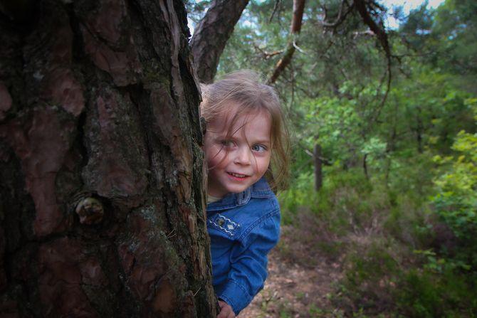 Miriam Ødegård dukker opp bak et tre.