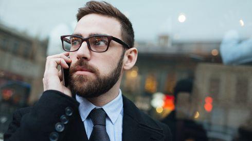 Pent kledd mann snakker i mobiltelefon utendørs.
