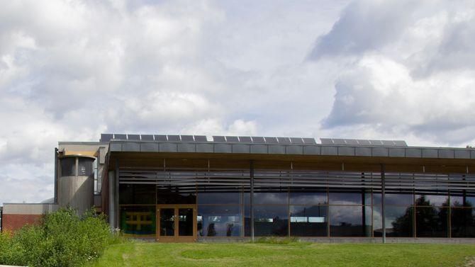Nadderudhallen har solfangere på taket. Tilknyttet hallen  (t.v.) står en av tre energisentraler som skal forsyne området med varme fra gropvarmelageret som mulig bygges på fotballbanen som ligger til venstre utenfor bildet.