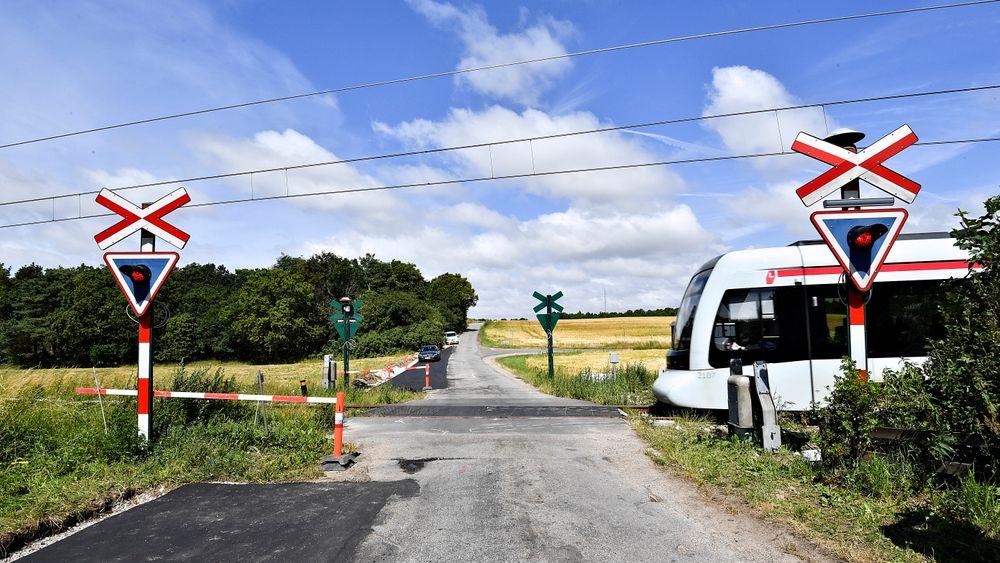 Et lettbanetog passerer ved stedet der en norsk mann og hans sønn mistet livet i en ulykke lørdag mellom en personbil og et lettbanetog i Trustrup på Djursland.