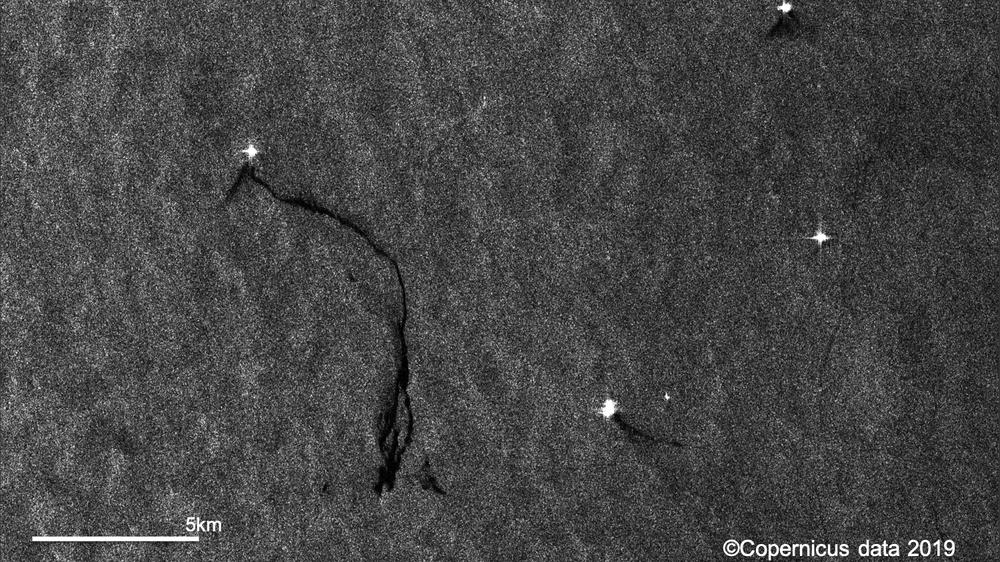 Radarbilde fra den europeiske satellitten Sentinel-1 over Nordsjøen den 11. juli som viser hvordan oljesøl kan ses i radarbilder som mørke flekker mot omkringliggende grått hav. De lyse punktene er plattformer eller skip som gir sterke refleksjoner i radarbilder. Contains modified Copernicus Sentinel data [2019].