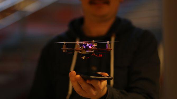 Henning Pedersen i bakgrunnen med en flyvende drone i forgrunnen.