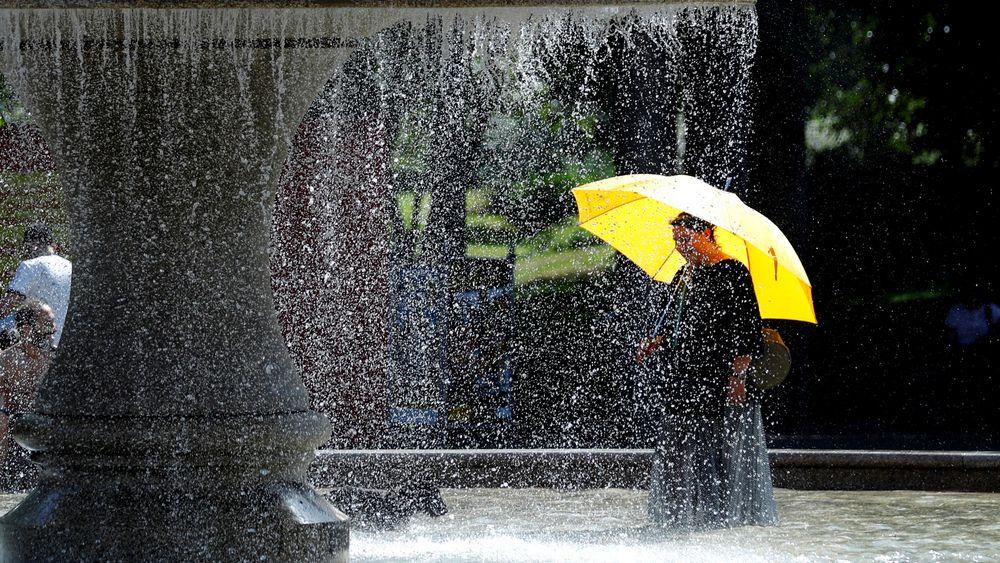 En kvinne kjøler seg ned i fontenen i Frankfurt torsdag.