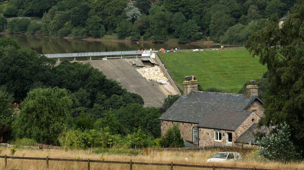 Vannmagasinet Toddbrook Reservoir like ved den lille byen Whaley Bridge i Derbyshire i England lørdag. Siden da har hjelpemannskaper pumpet vannstanden ned ytterligere 3,5 meter og helikoptre har sluppet 530 tonn sandsekker for forsterke den ødelagte murveggen.
