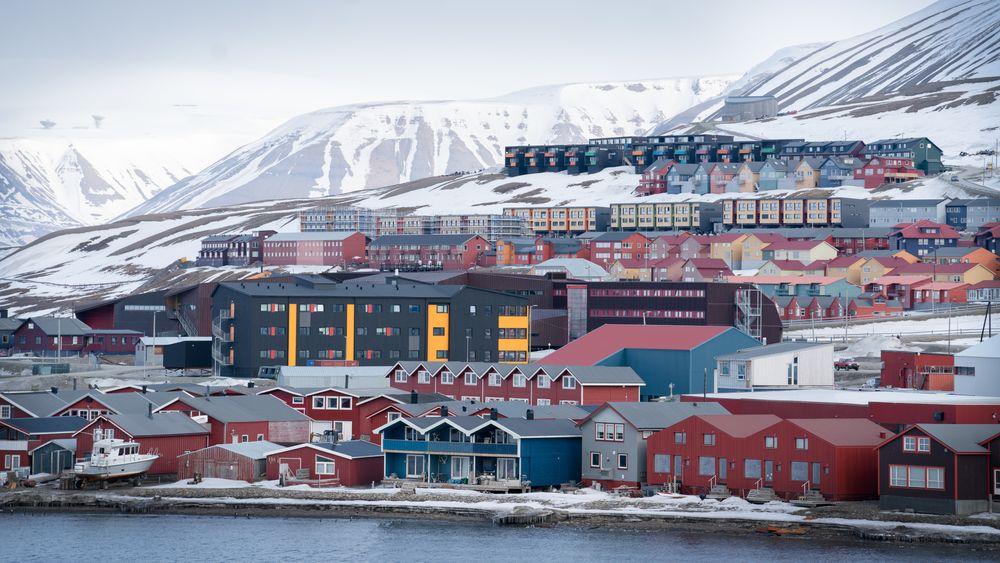 Bygningene i Longyearbyen synker mer enn de målte bygningene andre steder på Svalbard. UNIS' relativt nye gjestehus (grå og gul bygning midt i bildet) sank i fjor med 8 millimeter på flere av målepunktene.