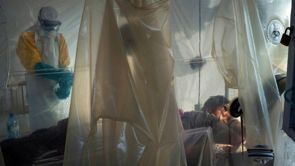 Helsepersonell iført beskyttelsesutstyr undersøker en pasient som ligger i isolat ved et behandlingssenter for ebola i Beni i Kongo.
