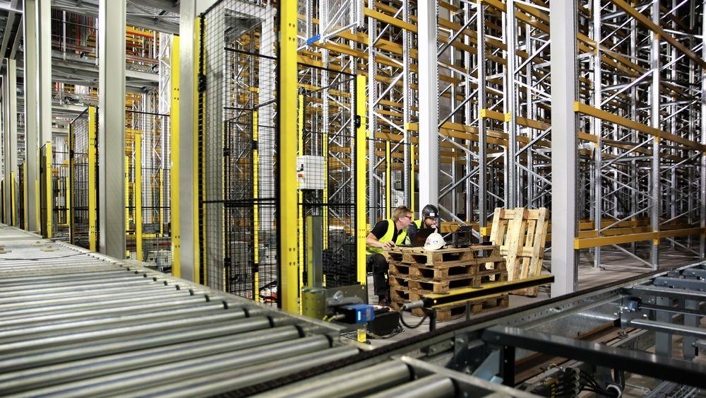 På høytlageret er det 65.000 palleplasser. Pallene løftres til og fra rullebåndet av 11 kraner, én for hver mast. Hver kran betjener 120 meter med reoler.