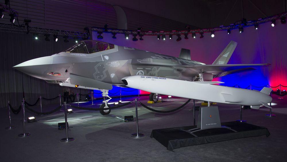 Utrulling av det norske F-35-flyet AM-1 med en JSM-modell ved siden av.