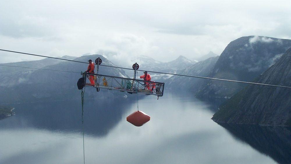 Man kan ikke ha høydeskrekk hvis man skal bygge eller vedlikeholde kraftlinjer. Men nå mener NVE og Energi Norge at også prisen er for høy. Bilder er fra utskifting av flymarkører over Hellemofjorden i 2003.