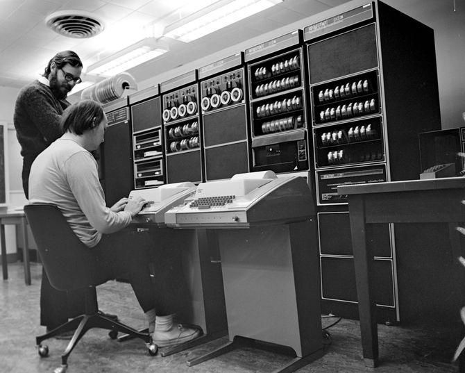 De to sentrale Unix-oppfinnerne, Dennis Ritchie (stående) og Ken Thompson, foran minidatamaskinen DEC PDP-11 og kabinetter med en hel del annet utstyr. Bildet er trolig tatt i 1972.