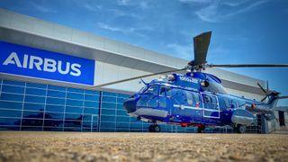 Et helikopter parkert utenfor en bygning med stor Airbus-logo