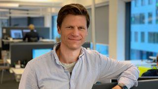 Senioringeniør i Rambøll Anders Lillemork Nilsen står i kontorlandskapet med blåstripete skjorte.