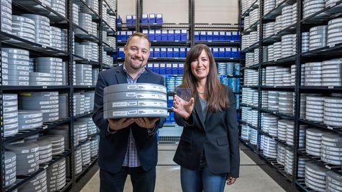 Brad Collar, sjef for globale arkiver og medieteknikk hos Warner Bros., holder fire filmruller med filmen «Superman» fra 1978, mens Vicky Colf, teknologidirektør i Warner Bros. holder en liten glassplate som i alle fall kan lagre innholdet på 22 slike filmruller.