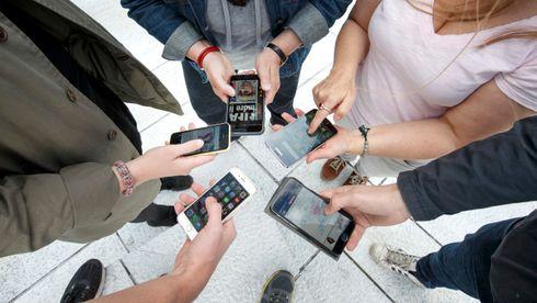 Fem hender med smarttelefoner i ring. Illustrasjonsfoto.