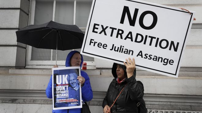 "Demonstranter utenfor en domstol i London, med plakater med ""No extradition – free Julian Assange""."