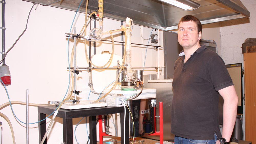 Gerrit Surup har tatt doktorgrad på bruk av fornybart trekull i metallurgisk industri. Her foran pyrolyseenheten, reaktorovn til høyre og oppsamling av pyrolyseolje i rør øverst i bildet.