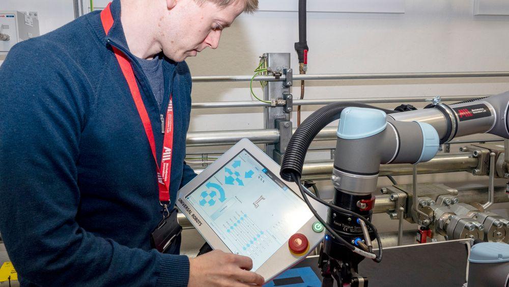 Halvor-Dag Settendal viser hvordan roboten styres ved hjelp av nettbrett. Programmeringen skal kunne gjøres av enhver operatør som behersker en smarttelefon.