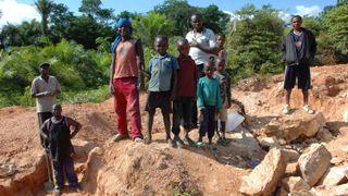 Foto av flere barn og et par voksne ved et steinbrudd.