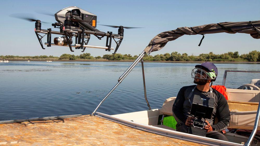I lufta: Fire kilo med kamera og stabilisatoroppheng. Operatøren bruker crickethjelp som sikkerhet når de skal ta imot droner som lander.