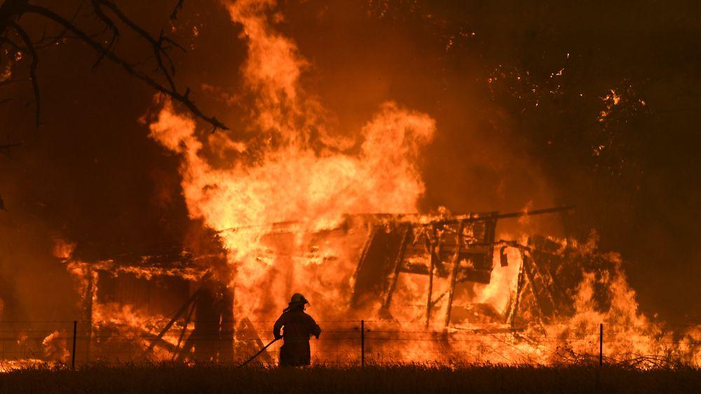 En brannmann kjemper mot flammene i Gospers Mountain i Bilpin, Australia. Nå har landet satt inn militære reservestyrker for å få bukt med krisa.