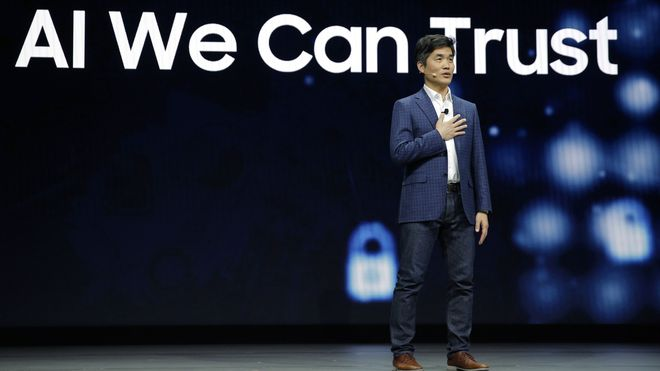 """Sebastian Seung på scenen, med teksten """"AI We can trust"""" på skjermen bak. Foto."""