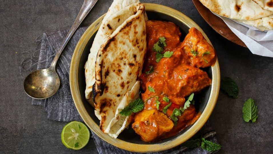 butter-chicken-served-with-homemade-indian-naan-bread-picture-id618457124