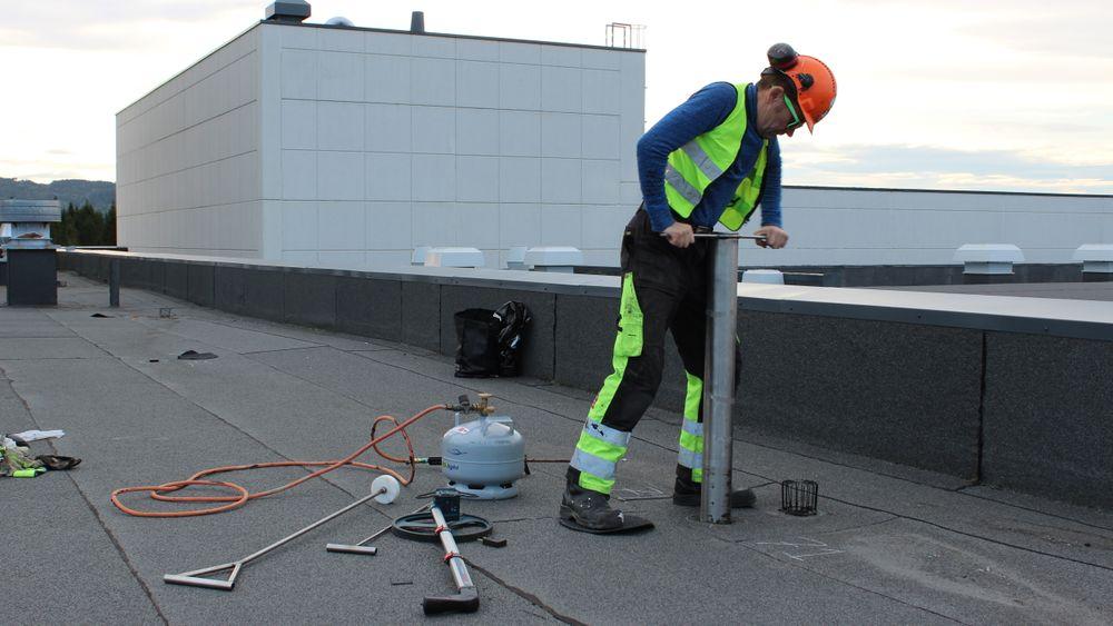 Tor Ove Nesset installerer en av sensoren på taket til Tine meierier i sommer.