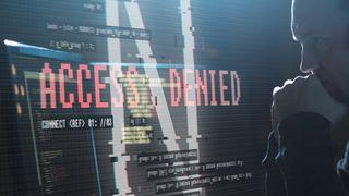 """Hacker ved en PC med med """"access denied""""-melding på skjermen."""