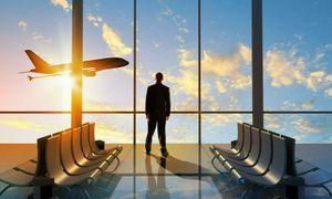 Foto fra innsiden av en flyplass med et fly som letter utenfor vinduet og en mann som ser ut