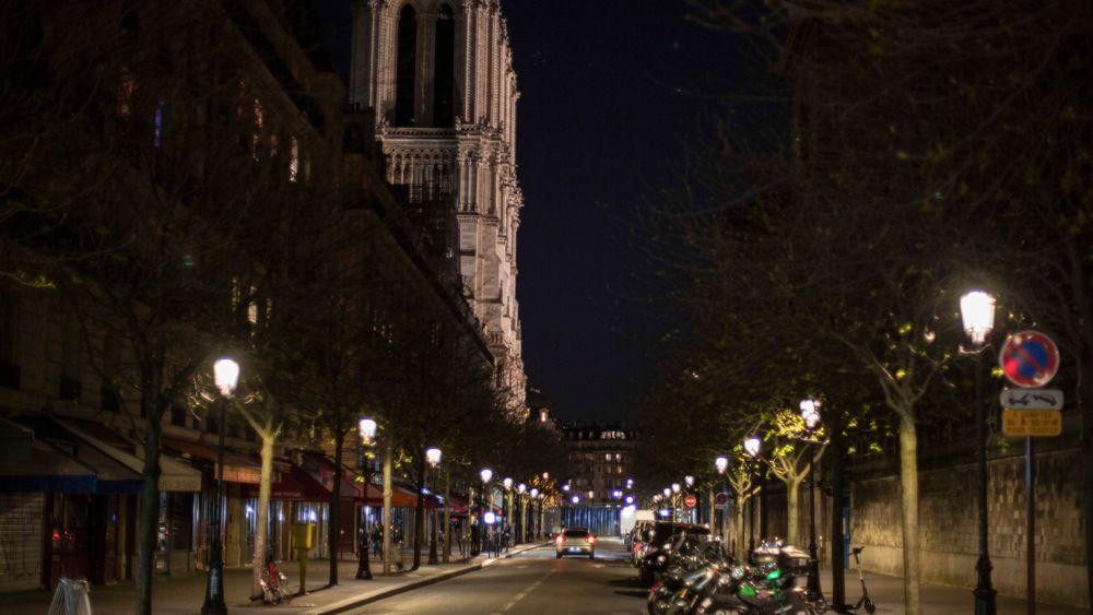 Svært få var ute i gatene ved Notre-Dame søndag grunnet myndighetenes restriksjoner. Nå utsettes også arbeidet på katedralen.