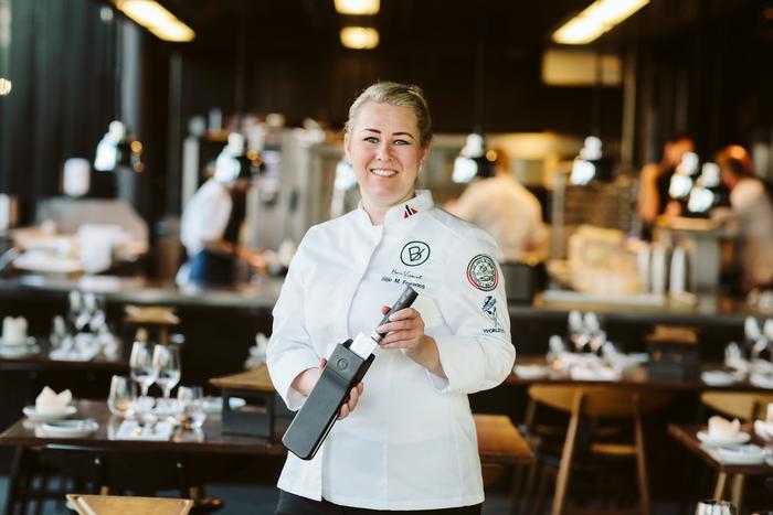 Bilde av Silje Merete Fossnes, grunnlegger av Bon Vivant, avbildet i en restaurant, mens hun holder hennes patenterte knivslire