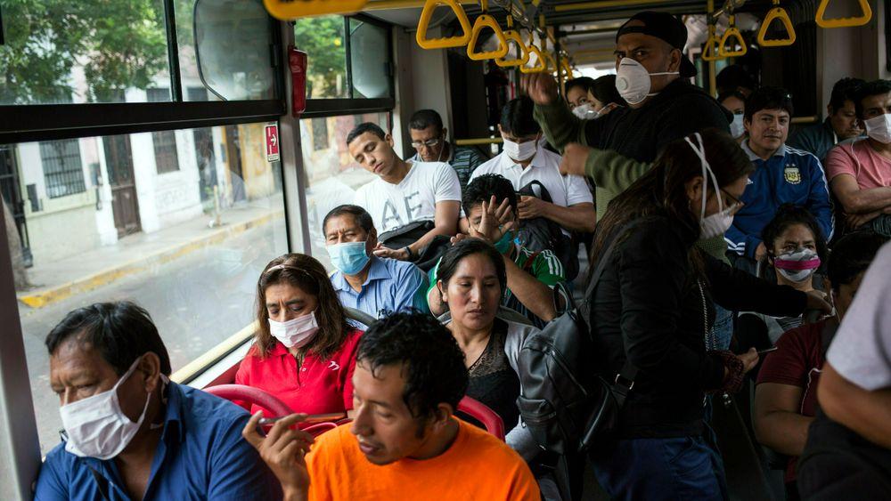 Passasjerer med munnbind på en buss i Perus hovedstad Lima. Landet erklærte mandag unntakstilstand.