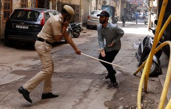En politimann I New Dehli deler ut slag for å straffe innbyggere som bryter karantenen.