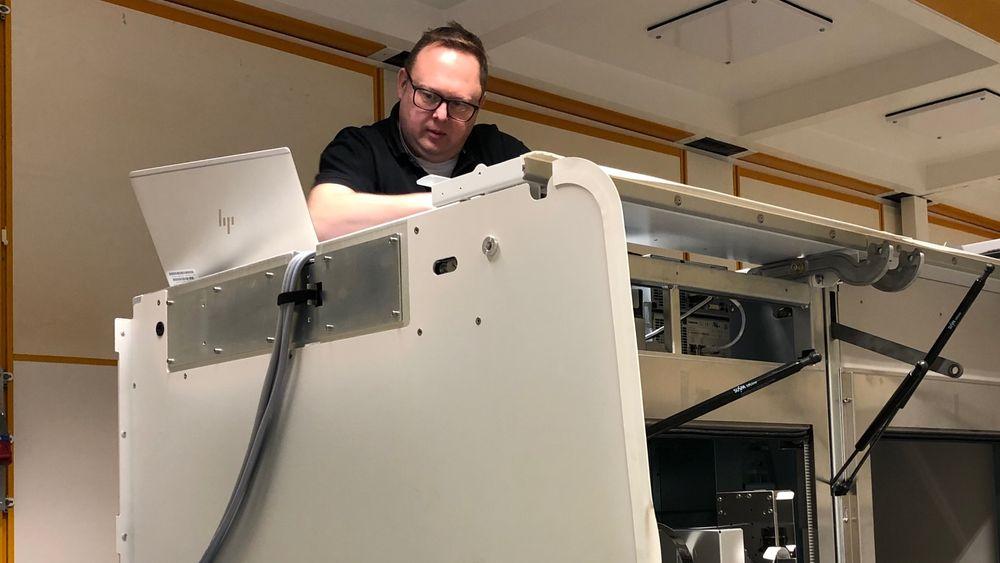 Serviceingeniør Martin Nielsen monterer en av de nye testmaskinene Cobas 6800 ved Oslo universitetssykehus.