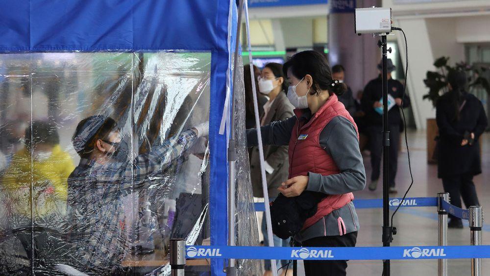 En kvinne som ønsker å ta toget fra Seoul, får temperaturen sjekket av en togansatt før ombordstigning. Sør-Korea har testet svært mange innbyggere for koronavirus og symptomer.
