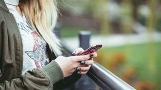 Kvinne holder mobiltelefon i hånden. Utendørs.
