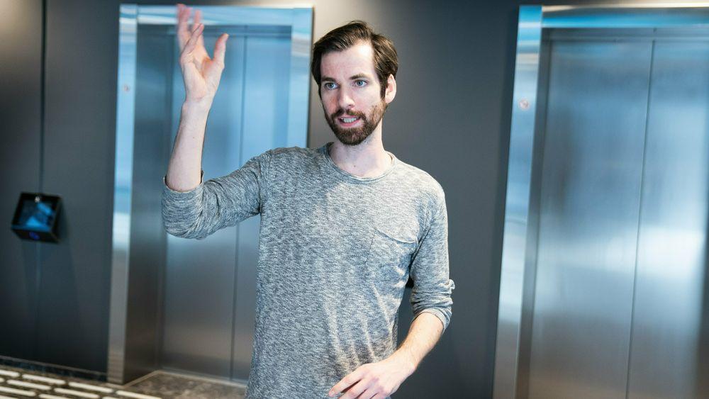 Eirik Bjørnstad foran de smarte heisene til Schindler i Karvesvingen 5 – «et av Europas smarteste bygg».