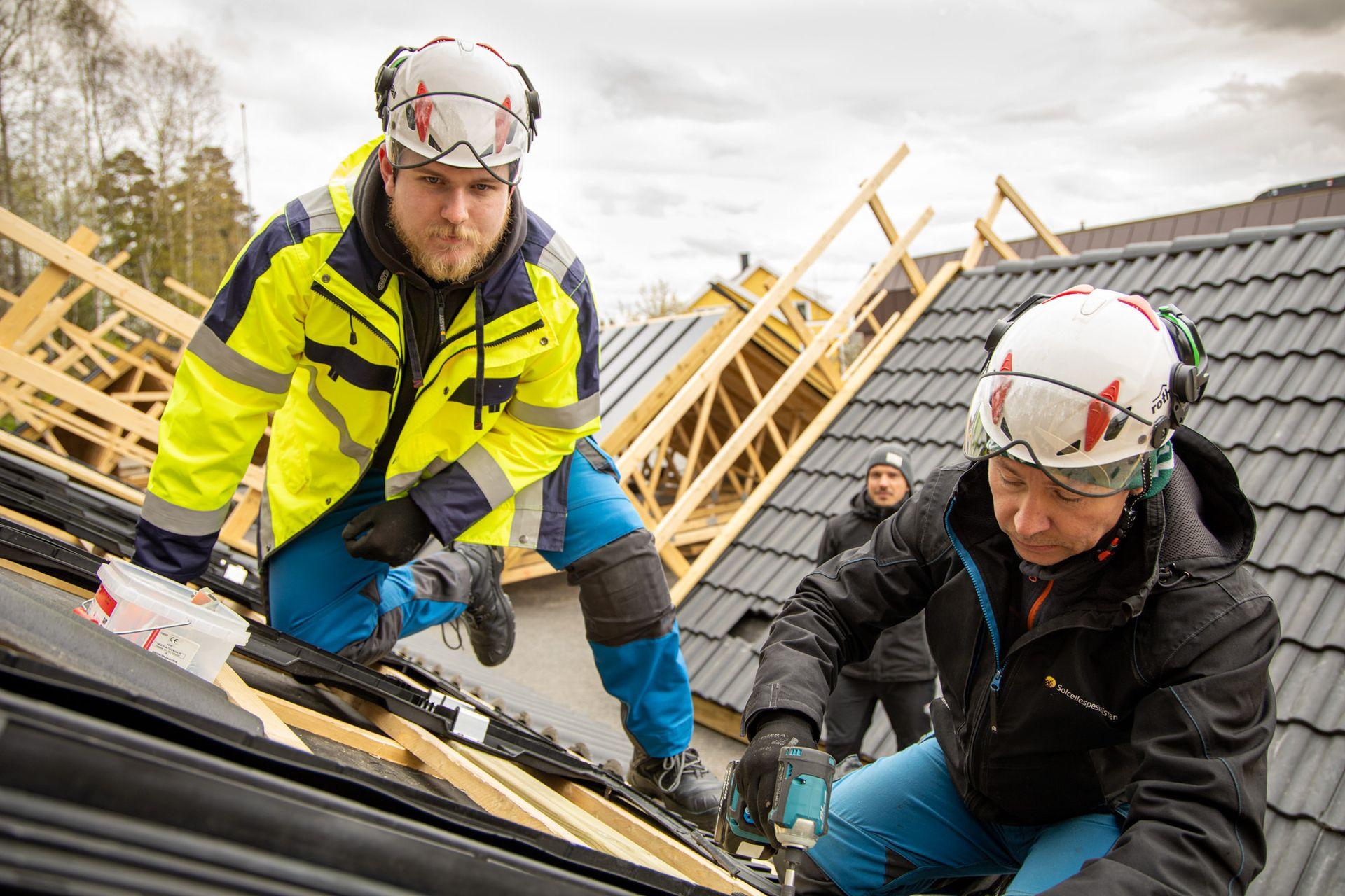 Simon Løining og Pedrag Kamenic monterer et integrert solcelletak, under kyndig veiledning av Ole Johannesen i bakgrunnen.