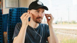 Mann som setter inn øreplugger/hodetelefon.
