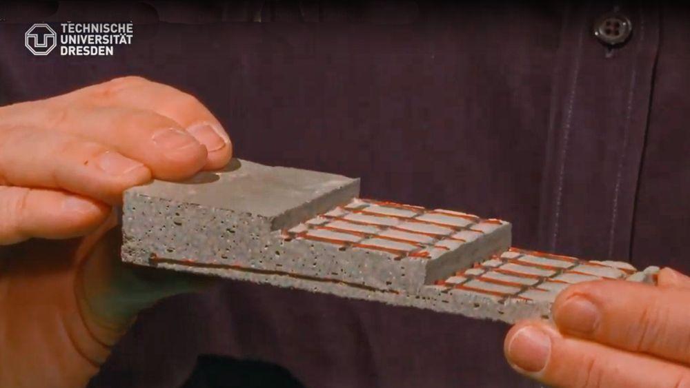 Professor Manfred Curbach viser frem en prøvestøp der betongen er armert med to lag netting av karbonfiber. Bildet er en skjermdump fra video.